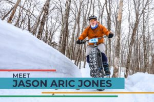 Jason Aric Jones riding mountain bike through woods in snow