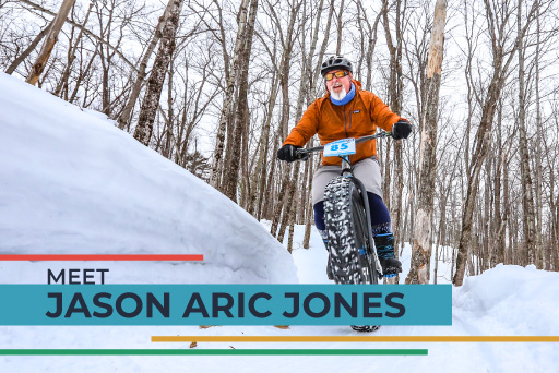 Jason Aric Jones riding mountain bike through woods in snow