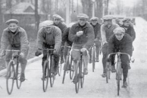 old image with group of cyclists eating energy bar