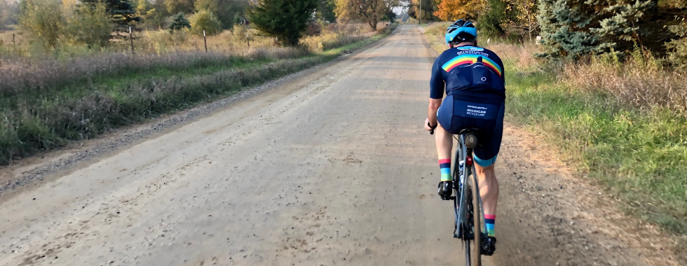 bicyclist-on-gravel-road-in-autumn