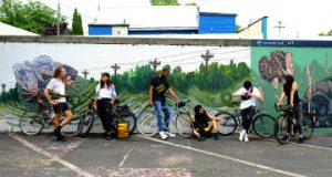 Group of Cyclists standing against painted wall with Wonder Goods gear